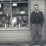 Portnacroish Shop 1950's. Angie Cameron (1911-1964), from Portnacroish, standing outside his shop. John MacFadyen, Laurel Cottage (today's Tigh na Croish) originally built the shop in the 1930's for his sister Teenie. Angie Cameron contracted polio during the WW2 while in the Navy, leaving him with the need to use callipers on his right leg. On his return from the war, the shop was purchased by the community with the help from the MacApline-Downies to enable Angie to start trading as the shop keeper. Source - Bertie Lawrie